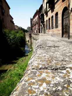 Along Carrera del Darro, by the river.