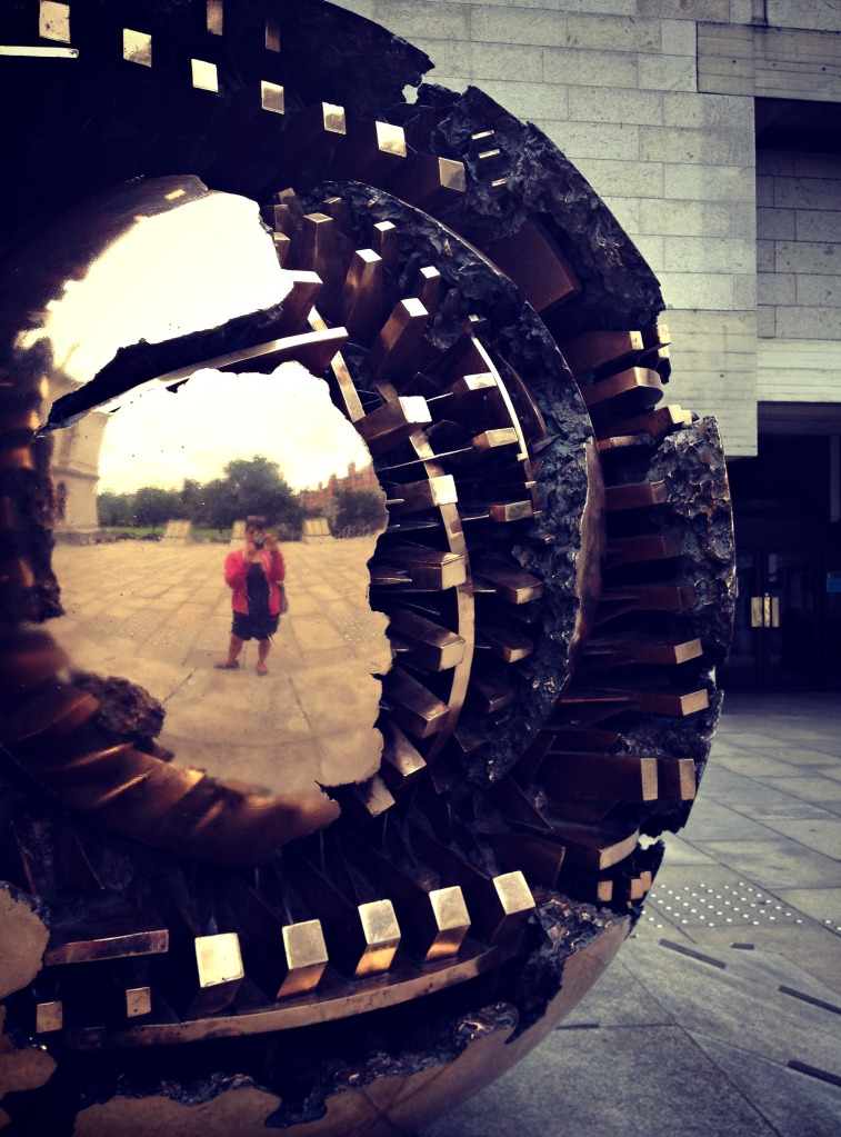 A reflection in Arnaldo Pomodoro's sculpture at Trinity College.