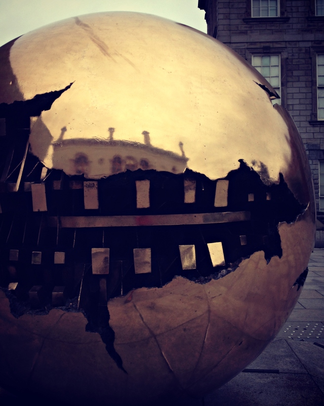 A reflection of Trinity College in Arnaldo Pomodoro's spherical sculpture.