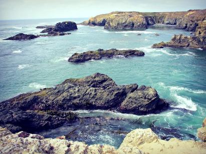 Sea, rocks, and sun.