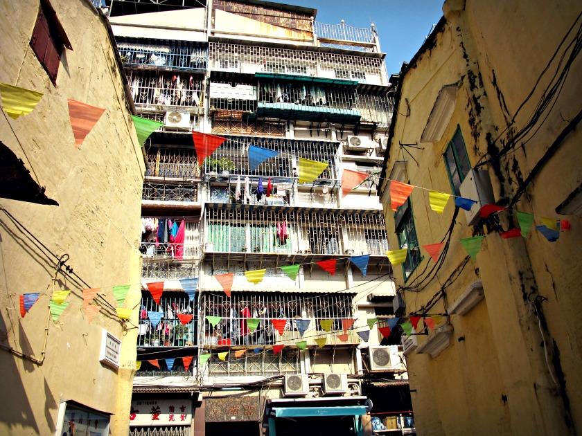 Colorful flags hanging in between buildings in the old town of Macau.