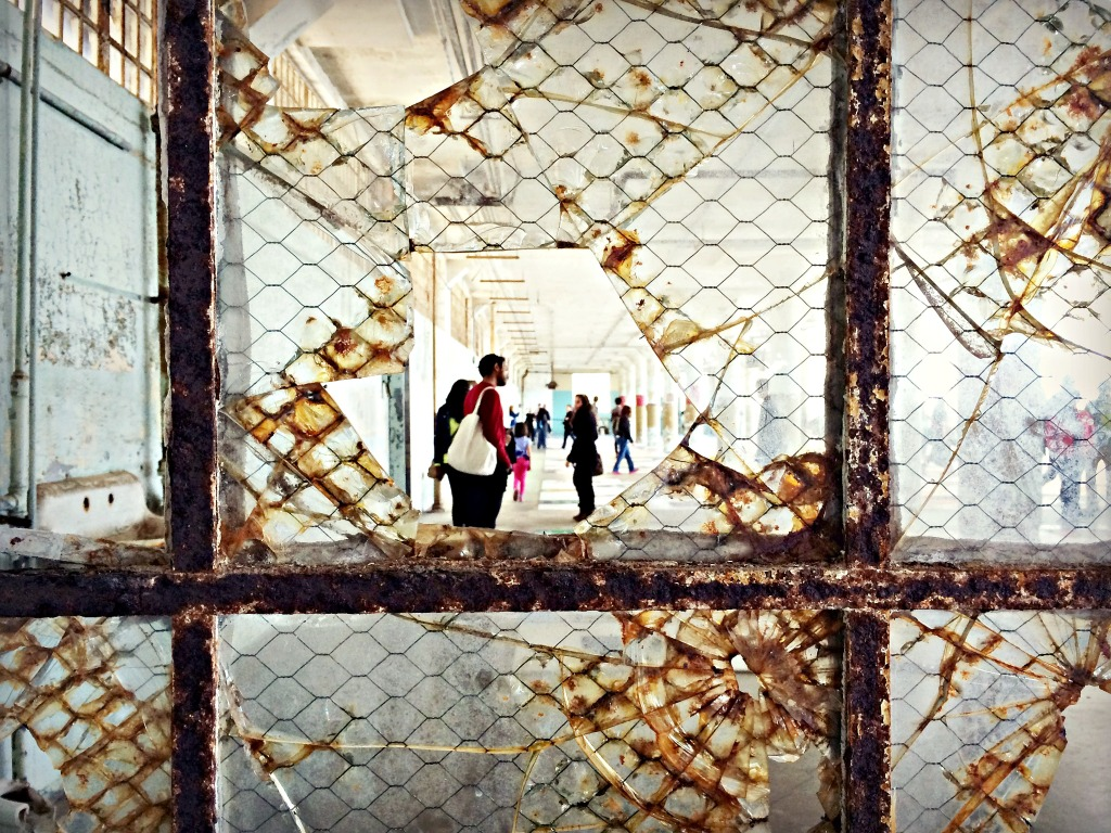 "A view through broken glass into the ""Trace"" exhibit of Lego portraits, in the New Industries Building."
