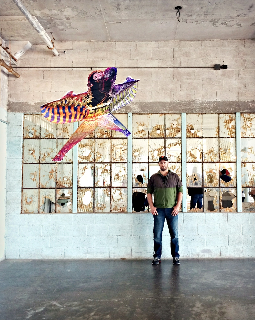"""A corner of the """"With Wind"""" installation, with winged bird-like creature, broken glass, and my husband Nick."""